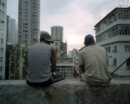 Reugees sit on a ledge overlooking the city